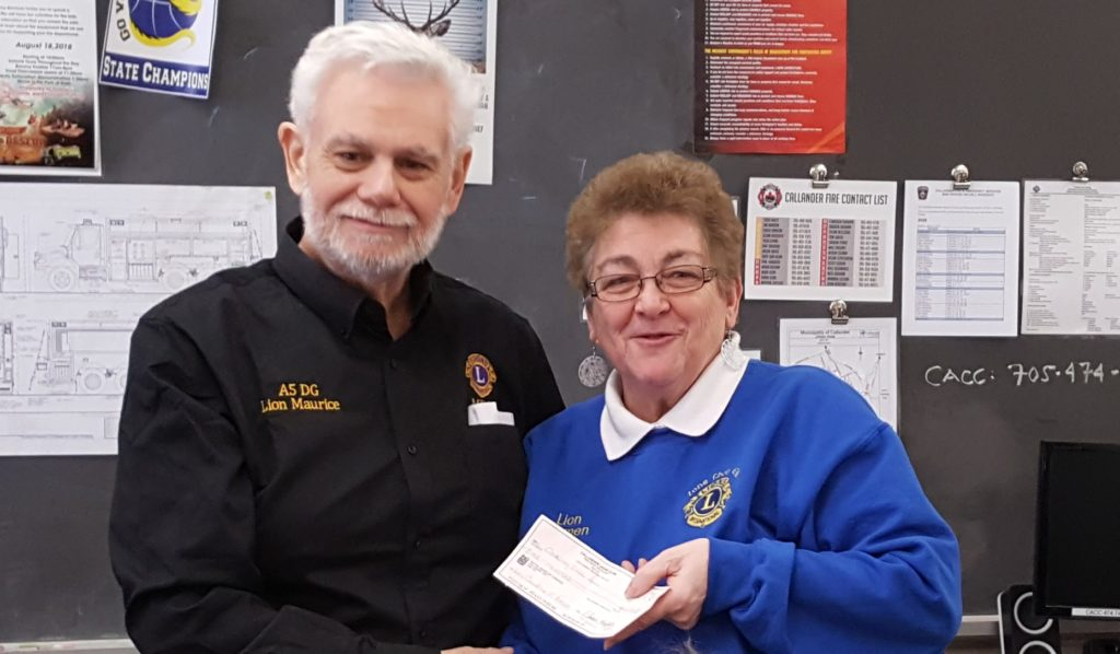 Callander Lions member PDG LIon Maurice Turgeon presents a cheque from the Callander LIons to 2nd VD Carmen Portelance, in support of the Leos attending the Forum